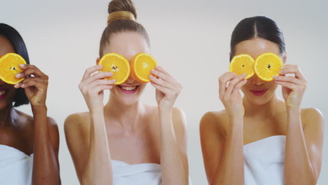Slow motion of beautiful young women of different ethnicities with perfect faces covering eyes with orange slices smiling in camera isolated on a white background. Slow motion of beautiful young women of different ethnicities with perfect faces covering eyes with orange slices smiling in camera isolated on a white background. serum sample stock videos & royalty-free footage