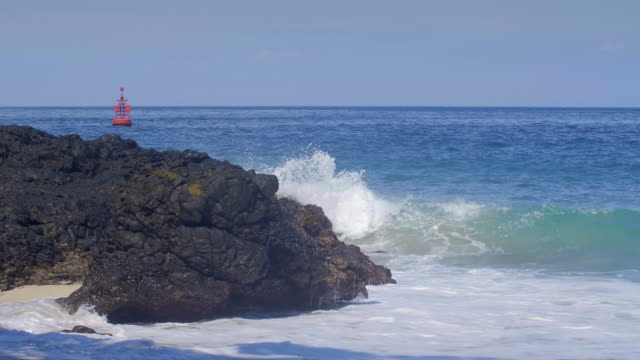 Slow motion of big waves with splashes on black rocky beach