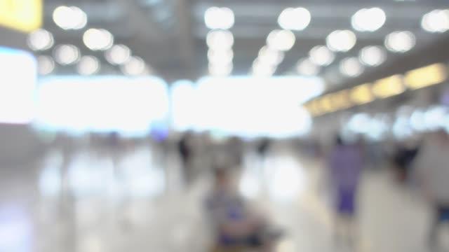vídeos de stock, filmes e b-roll de câmera lenta de blur viajante andando à partida terminal no aeroporto com luz de bokeh - desfocado foco