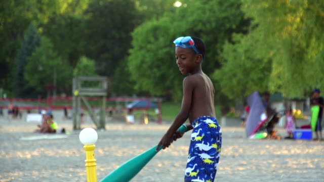 Slow Motion of boy playing baseball at beach video