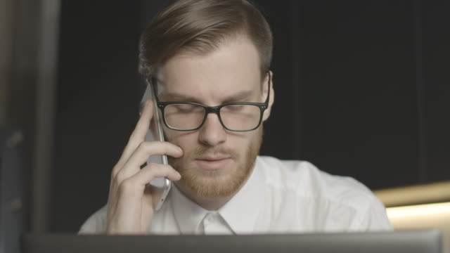 Slow motion of brunette man with red beard talking on the phone. Close-up of busy anxious Caucasian businessman indoors. Stress, overworking, lifestyle. Slowmo. Cinema 4k ProRes HQ.