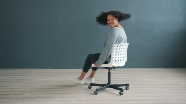 Slow motion of carefree Afro-American woman spinning on chair in studio video
