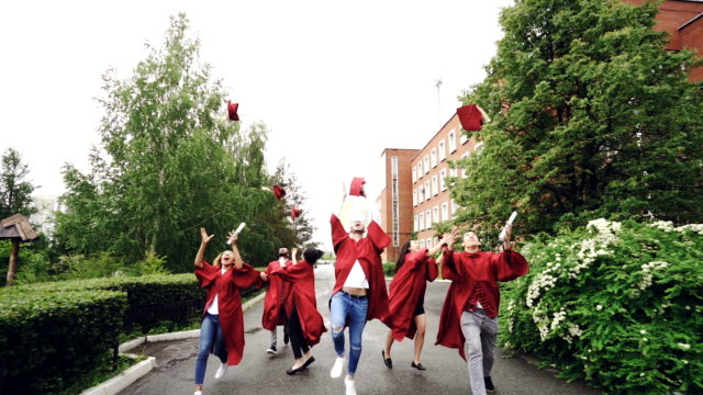 slow motion of cheerful friends students running on campus with diplomas, throwing mortarboard caps, catching them and laughing. end of studies and youth concept. - tocco accademico video stock e b–roll