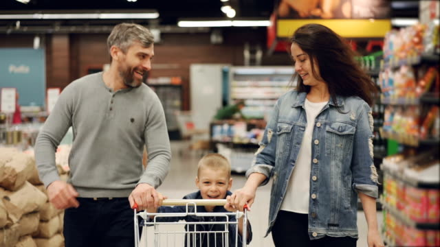 Slow motion of cheerful people happy family running in food store with shopping trolley and laughing, boy is pushing cart and his parents are helping him. Slow motion of cheerful people happy family running in food store with shopping trolley and laughing, boy is pushing cart and his parents are helping him. Fun in supermarket concept. woman pushing cart stock videos & royalty-free footage