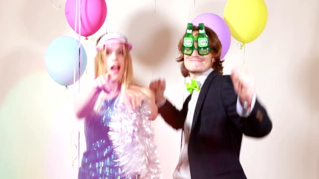 Slow motion of cheerful woman and man dancing in photo booth video