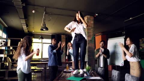 vídeos y material grabado en eventos de stock de cámara lenta de mujer alegre bailando sobre mesa de oficina en fiesta corporativa, mientras que sus colegas están de pie, mirándola, palmas de las manos y riendo. - rusia