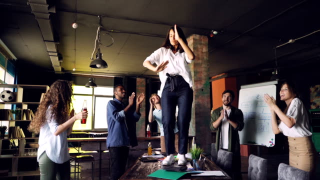slow motion of cheerful woman dancing on table in office at corporate party while her colleagues are standing around, looking at her, clapping hands and laughing. - праздничное событие стоковые видео и кадры b-roll