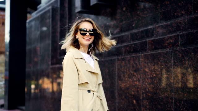 slow motion av glad ung kvinna dans på gatan som lyssnar på musik med hörlurar med smartphone. modern teknik, roliga och glada människor koncept. - elegans bildbanksvideor och videomaterial från bakom kulisserna