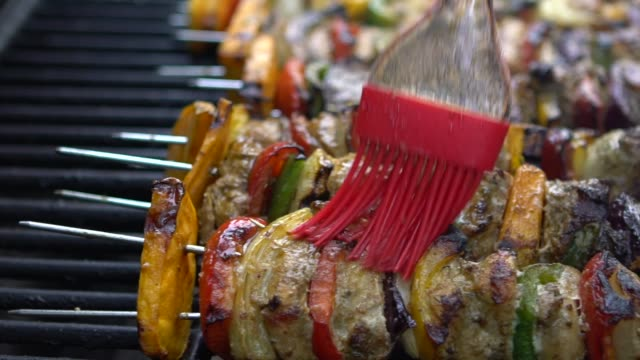 Slow Motion of chef covering with sauce the delicious skewers on BBQ grill. Slow Motion of chef covering with sauce the delicious skewers on the BBQ grill. Cooking brochette on grilled meat. Food cooked with grilling barbecue. Man cooking in backyard of house-Dan skewer stock videos & royalty-free footage
