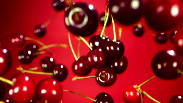 Slow motion of cherry fly in the air Close-up of cherry rotates in the air on a red background, Slow motion cherry stock videos & royalty-free footage