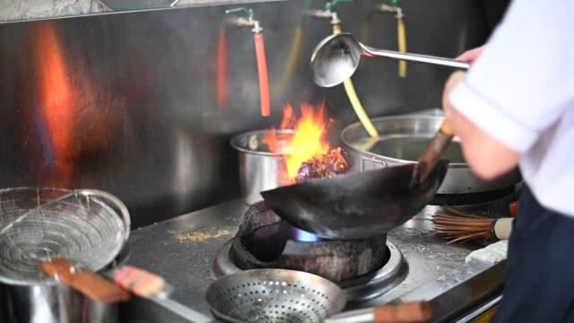 vídeos de stock, filmes e b-roll de câmera lenta do alimento chinês asiático de cozimento principal com wok no fogão a gás hd flaming vegetais na frigideira, movimento lento - comida chinesa