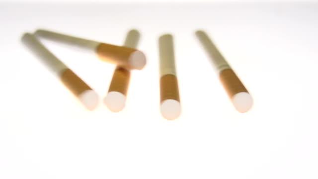 slow motion of cigarettes falling on white - nikotin stok videoları ve detay görüntü çekimi