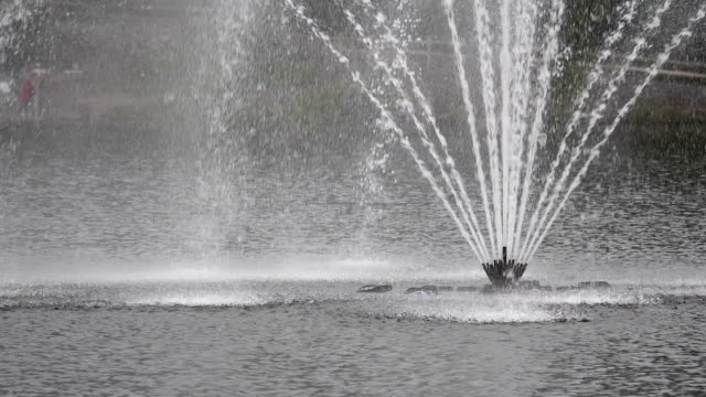 Slow motion of city park fountain jet in the lake video
