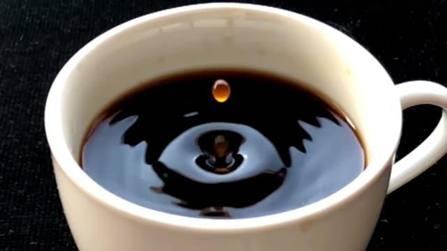 vídeos y material grabado en eventos de stock de 4 k lenta de café gota caer en una taza. - café negro