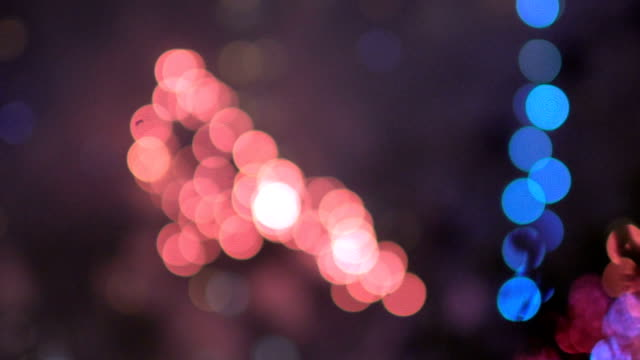 Slow motion of colorful bokeh lights circles from new year celebration fireworks on night city street. Abstract background video