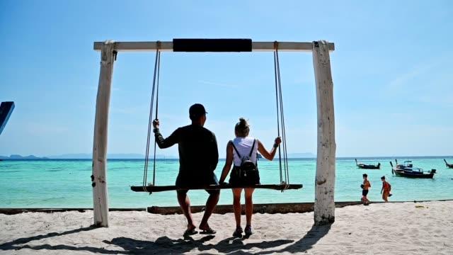 vidéos et rushes de ralenti de couples s'asseyant sur la balançoire en bois sur la plage en mer tropicale à l'île de lipe - mer d'andaman
