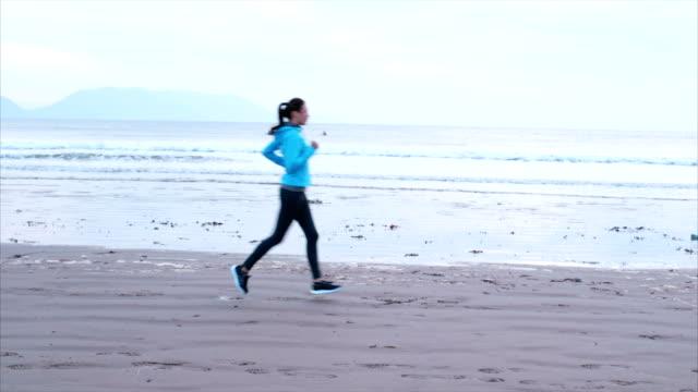 スローモーションの決定若い女性ビーチでジョギングをお楽しみください。 - 全身点の映像素材/bロール