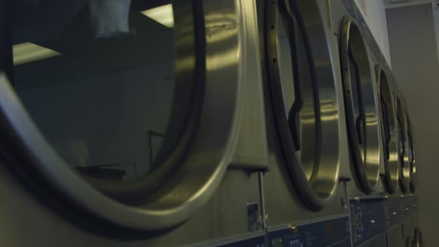 Slow motion of dryer machines spinning at laundromat video