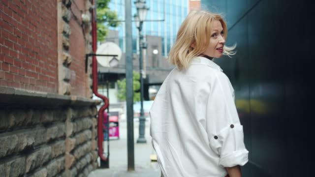 vidéos et rushes de mouvement lent de dame mûre élégante marchant à l'extérieur tournant regardant l'appareil-photo - femmes d'âge mûr