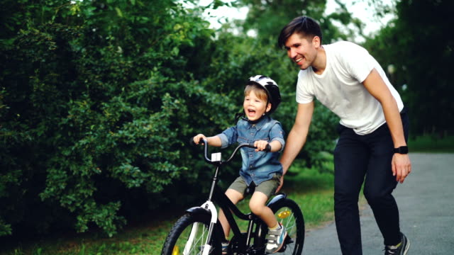 Slow motion of excited boy riding bicycle and laughing while his careful father is helping him holding bike and teaching child to ride. Family, sports and childhood concept.