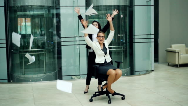 vídeos de stock e filmes b-roll de slow motion of excited businesswomen whirling in rolling chair and throwing papers in air, laughing and having fun. positive emotions, work and coworkers concept. - chair