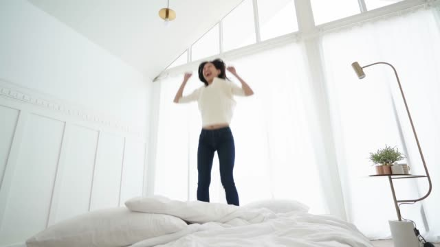 slow motion of exited asian woman jump over white bed in bedroom with energy and happiness success lifestyle ideas concept