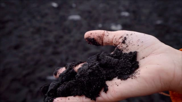 Slow motion of female holding black sand in hand falling back to the ground video