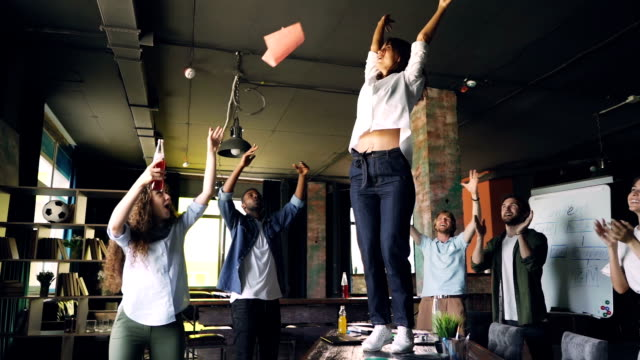 vídeos de stock e filmes b-roll de slow motion of female manager dancing on desk at corporate party and throwing pile of documents in air while team members are laughing and clapping hands. - descuidado