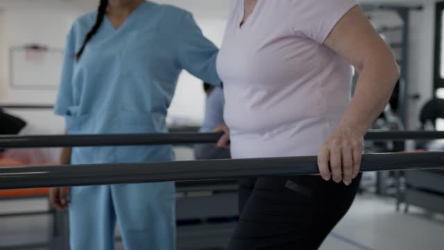 平行棒と女性セラピストの助けを借りて歩く女性患者のスローモーションは、両側で彼女を支援します - 医療スクラブ点の映像素材/bロール