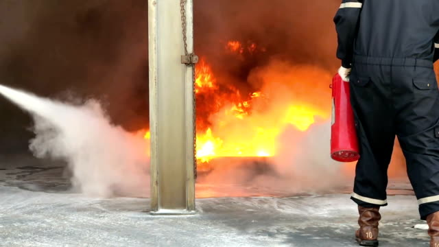 slow motion of fire fighting training by dry powder, fire extinguisher, water spray and foam for heavy industry or oil and gas industrial - gommapiuma video stock e b–roll