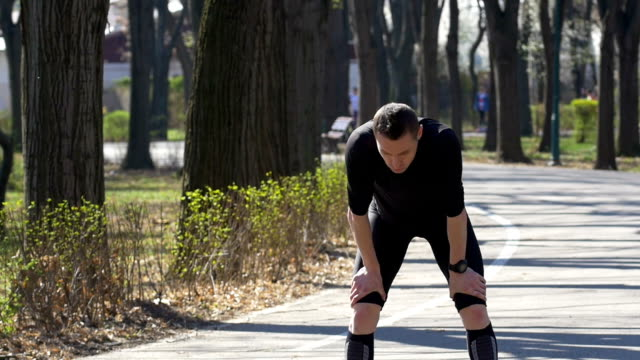 Slow motion of fit male jogger after a quick break catching breath resumes running in park setting smartwatch tracker video
