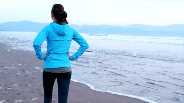 Slow motion of fit woman walking with hands on hips at shore after run video