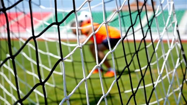 Slow motion of footballer soccer player training, football net in front