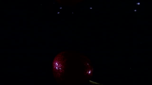 Slow motion of fresh cherry falling in water video