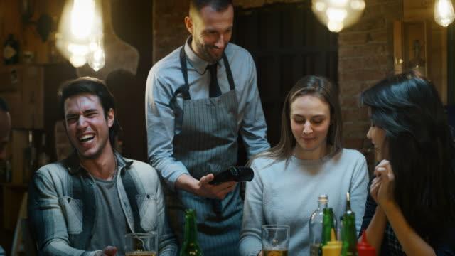 zwolniony ruch przyjaciół płacących rachunek po zjedzenie posiłku w restauracji lub pubie. - credit card filmów i materiałów b-roll