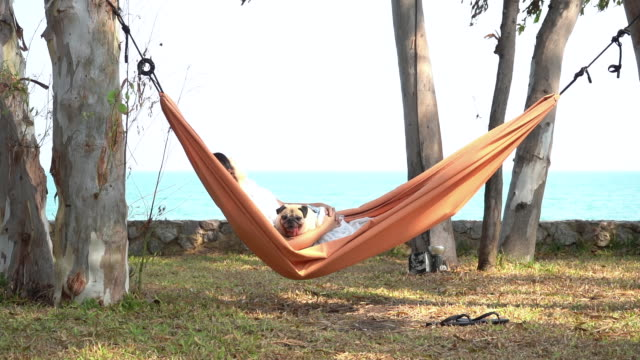Slow Motion of funny cute pug dog smiling and tongue sticking out while on a trip with her owner, joyful young family, woman lying rest in comfortable hammock on sea beach. Happy times concept