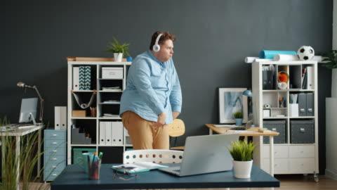 vídeos y material grabado en eventos de stock de movimiento lento de empleado divertido bailando en la sala de oficina usando auriculares - bailar