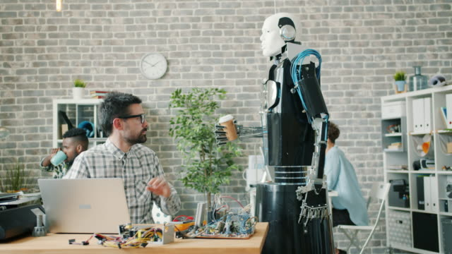 Slow motion of futuristic robot bringing coffee to young researcher in laboratory