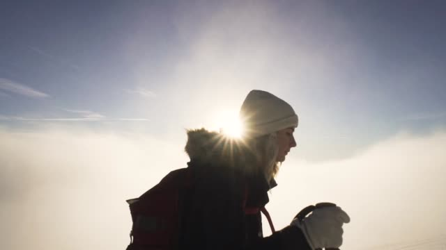 slow motion of girl hiking on snow in slovak mountains above clouds during sunset in winter - trekking sul ghiaccio video stock e b–roll