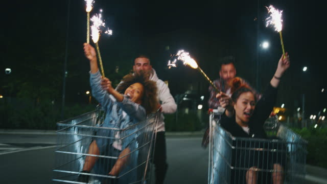 Slow motion of group of young friends of different ethnicities are having fun together racing on shopping carts at supermarket parking at night Slow motion of group of young friends of different ethnicities are having fun together racing on shopping carts at supermarket parking at night. woman pushing cart stock videos & royalty-free footage