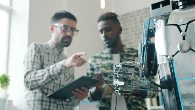slow motion di ragazzi che testano robot con tablet, braccio mobile macchina intelligente - braccio umano video stock e b–roll