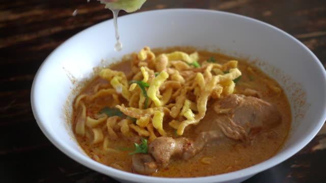 vídeos y material grabado en eventos de stock de slow motion of hand putting lime in khao soi, thai northern noodle - cebolla