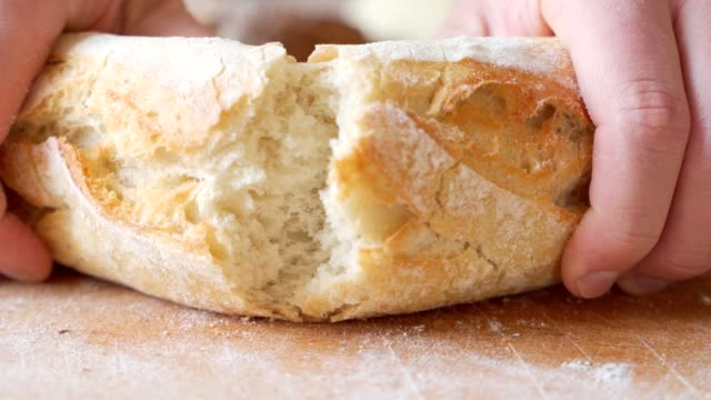 Slow motion of hands breaking a freshly baked loaf of bread