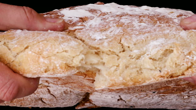 vídeos de stock, filmes e b-roll de movimento lento das mãos quebrando um pão acabado de cozer - sem glúten