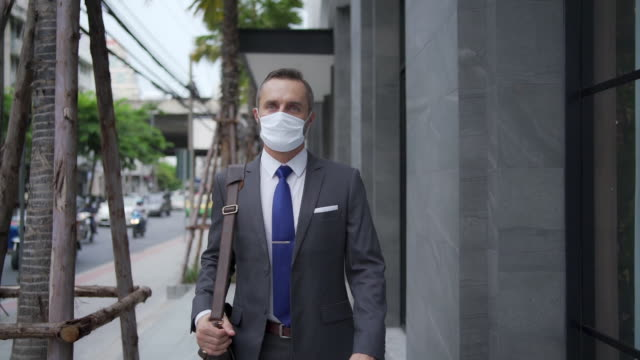 HD Slow motion of Handsome Caucasian business man office worker in suit and leather bag walking in city street to office district for working. Businessman wearing face mask during protect covid-19 virus pandemic and air pollution. New normal concept.
