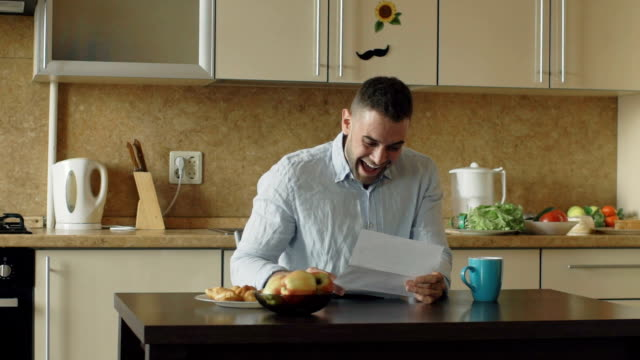 Slow motion of Handsome man recieve good news reading letter in the kitchen while have breakfast at home video