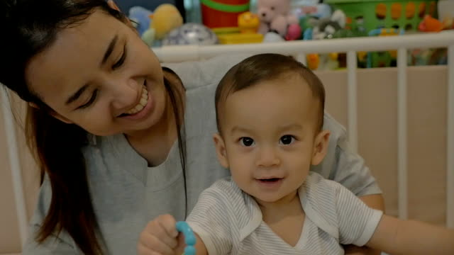 Slow motion of Happy Asian baby boy playing bike toy with his mother