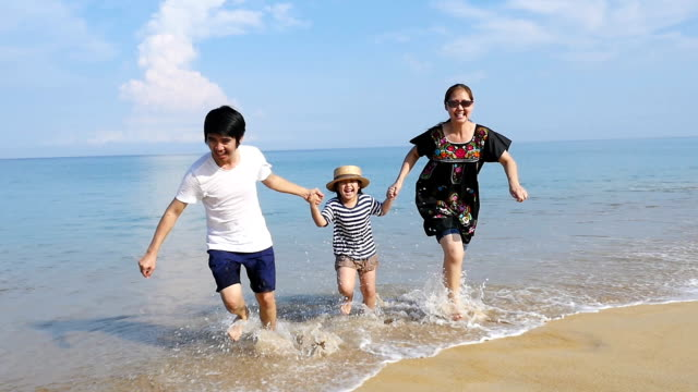 Slow motion of Happy Asian family running on the sand beach together video