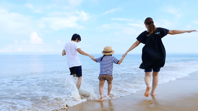 Slow motion of Happy Asian family running on the sand beach together, Phuket Thailand video