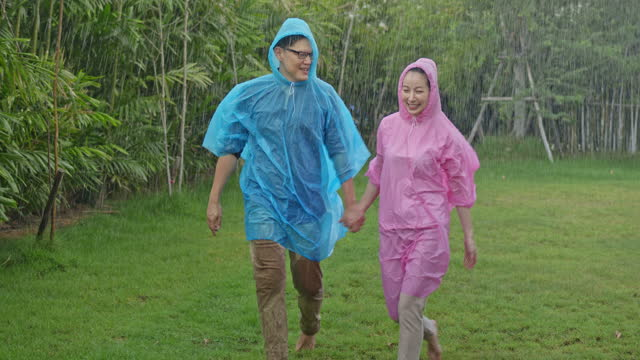 Slow motion of happy couple in love are walking under the rain in the garden